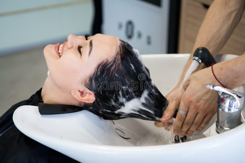 Haarpflegeverfahren im Schönheitssalon Friseur bürstet Frau ` s Haar, das eine Behandlungsmaske oder -conditioner verbreitet stockbild
