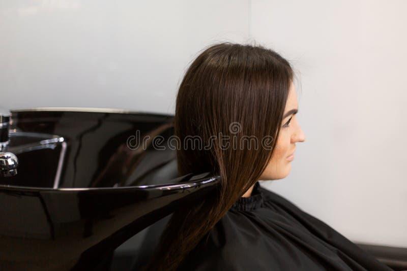 Haarschnittmeister w?scht Haar ihres Kunden hatte lizenzfreie stockfotografie
