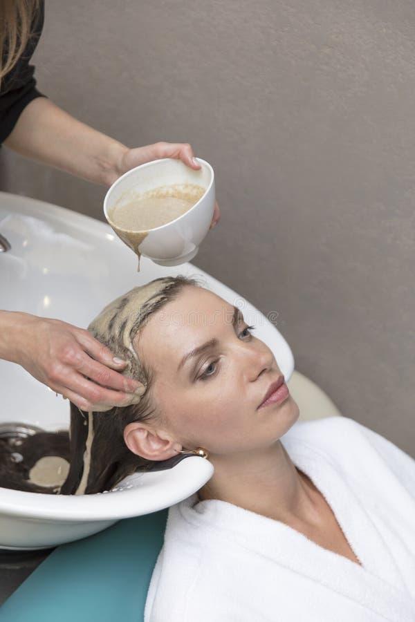 Haarschoonheidsverzorging, vochtinbrengende crèmetoepassing, kapper, haarmasker van een mooie meisje, natuurlijk, een gezondheid  stock foto