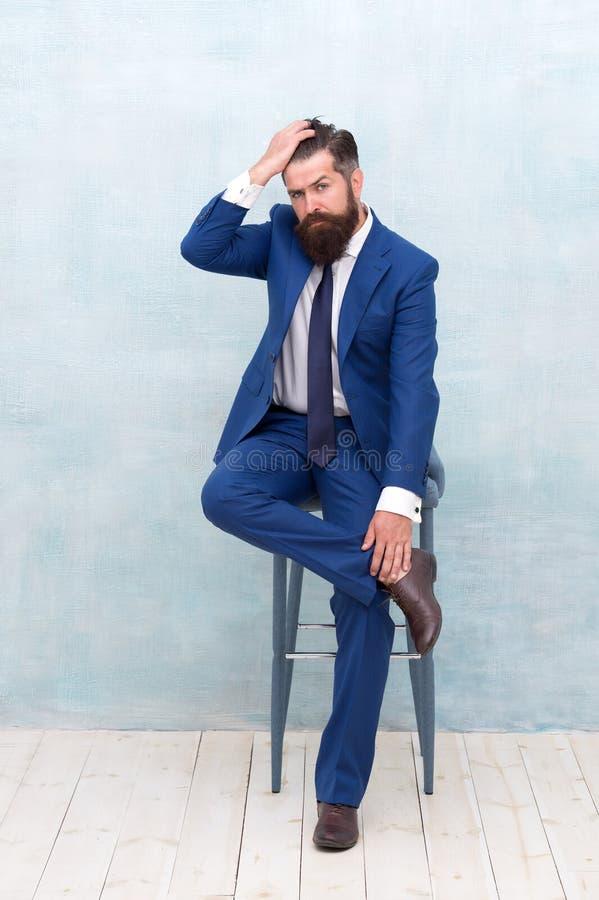 Haarsnede voor elke stijl Gedekte man aanraakt haar Unshaven zakenman in formalwear zit op stoel Barbershop stock fotografie