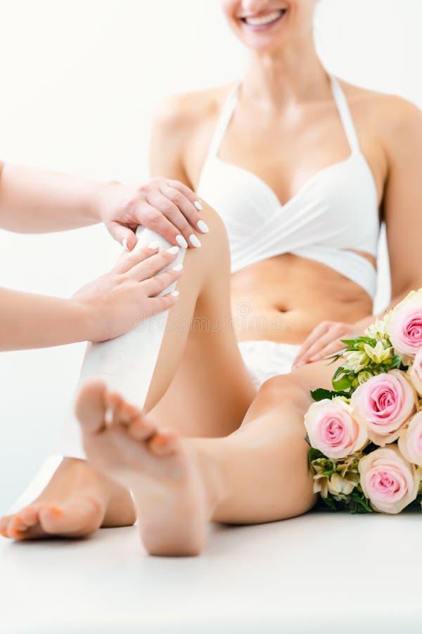 Haarverwijdering die wasstroken gebruiken bij de benen in schoonheidssalon royalty-vrije stock afbeeldingen