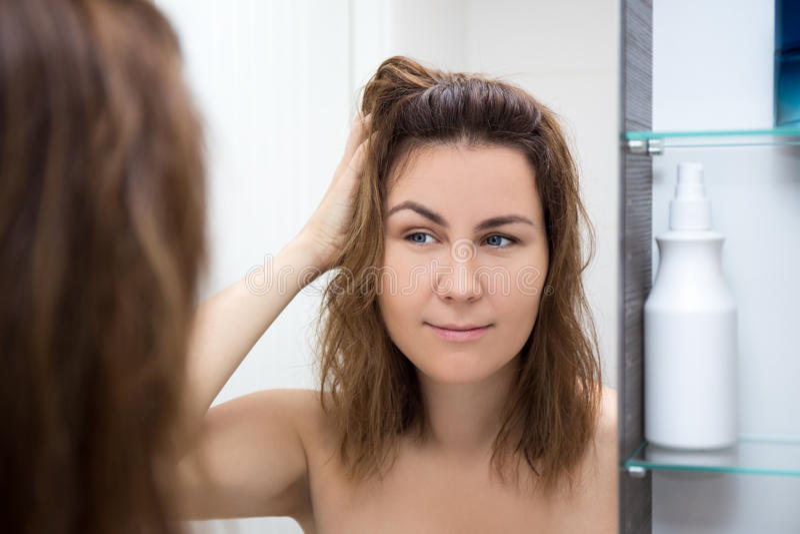 Haarverzorgingconcept - gelukkige vrouw die spiegel bekijken stock afbeelding