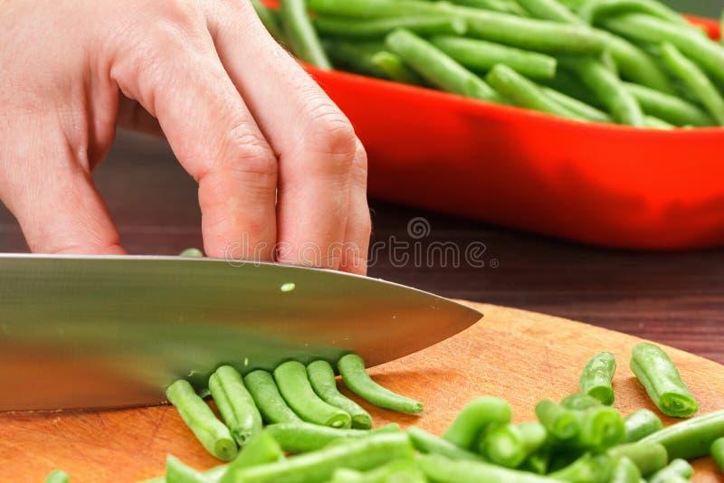 Habas del corte del cocinero para cocinar Acción para arriba en la comida del invierno imagen de archivo