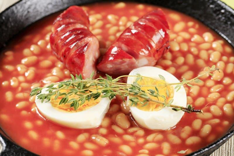 Habas en salsa y salchicha de tomate imagenes de archivo