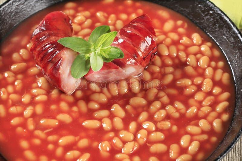 Habas en salsa y salchicha de tomate imagen de archivo