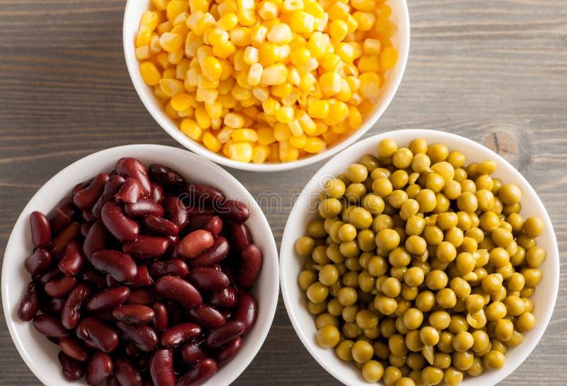 Habas rojas, guisantes verdes y maíz dulce en los cuencos blancos imagen de archivo libre de regalías