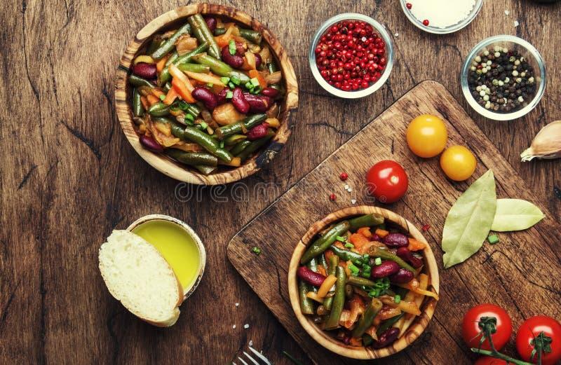 Habas verdes con las verduras, las setas y los tomates Comida que cocina el fondo, tabla r?stica de madera del vintage Copie el e fotografía de archivo
