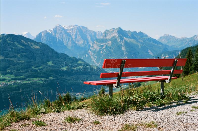 Haben Sie einen Rest in den Schweizer Alpen mit einer schönen Ansicht über eine hölzerne rote Bank lizenzfreie stockfotografie