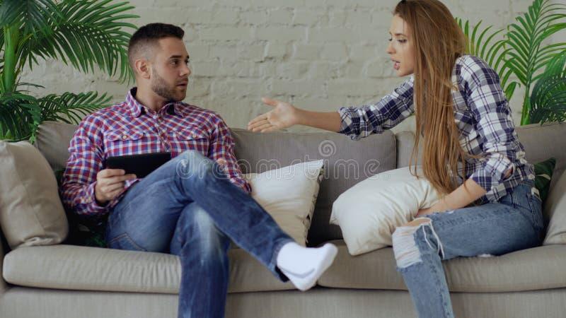 Haben umgekippter Paarstreit der Junge wegen des Mannes Internet-Sucht und seinen girlfrieng Ruf auf ihm versuchend sich zu entfe stockbild