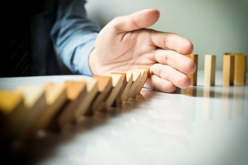 haber derribado continuo o riesgo de los dominós de la parada de la mano del hombre de negocios con c imagen de archivo