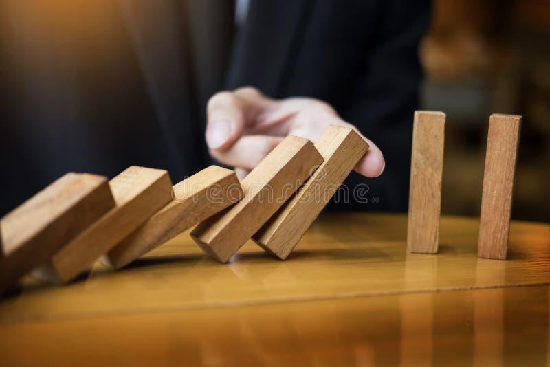 haber derribado continuo o riesgo de los dominós de la parada de la mano del hombre de negocios con c fotos de archivo