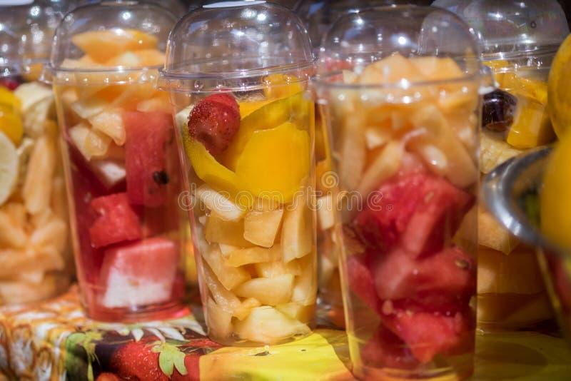 Haber tajado fresco y los pedazos da fruto en tazas plásticas para llevarse vendido en el mercado local foto de archivo