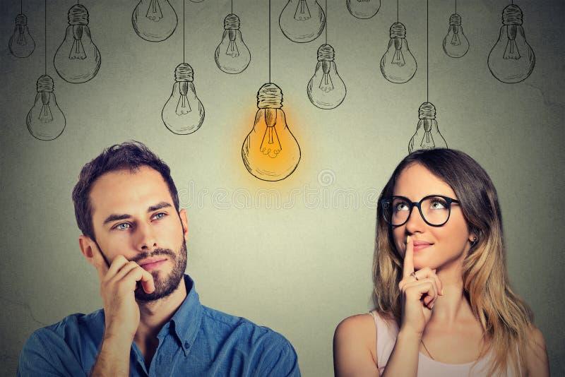 Habilidades cognoscitivas masculinas contra hembra Hombre y mujer que miran la bombilla imagenes de archivo