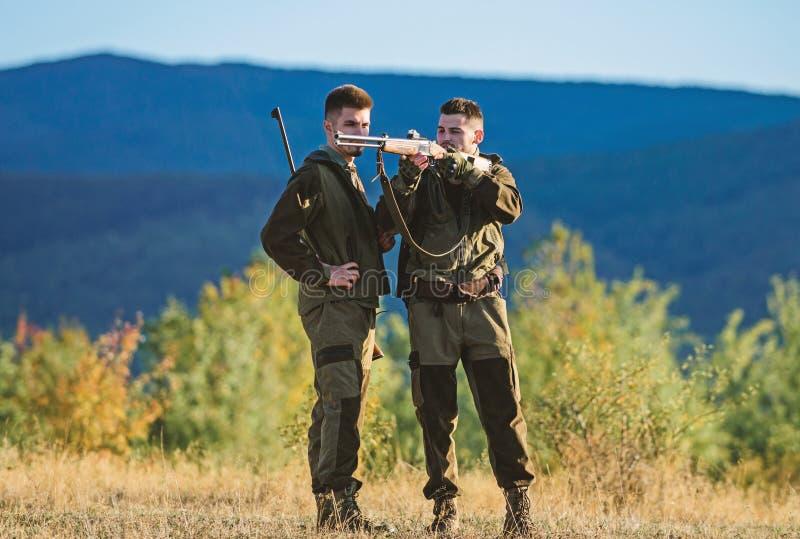 Habilidades de la caza y equipo del arma C?mo caza de la vuelta en la afici?n Amistad de los cazadores de los hombres Fuerzas del fotos de archivo
