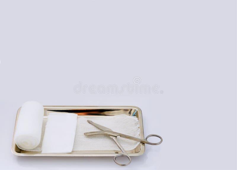 Habillage de l'ensemble de blessure, ciseaux, gaze de petit pain, gaze de protection, plateau sur le petit morceau photos stock