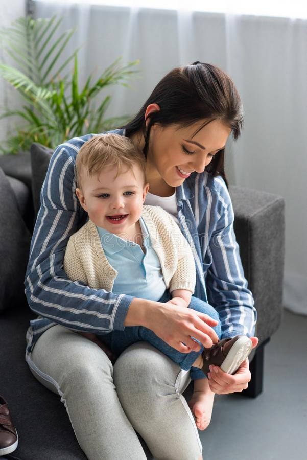 habillage de mère gai petit bébé sur le sofa photos libres de droits