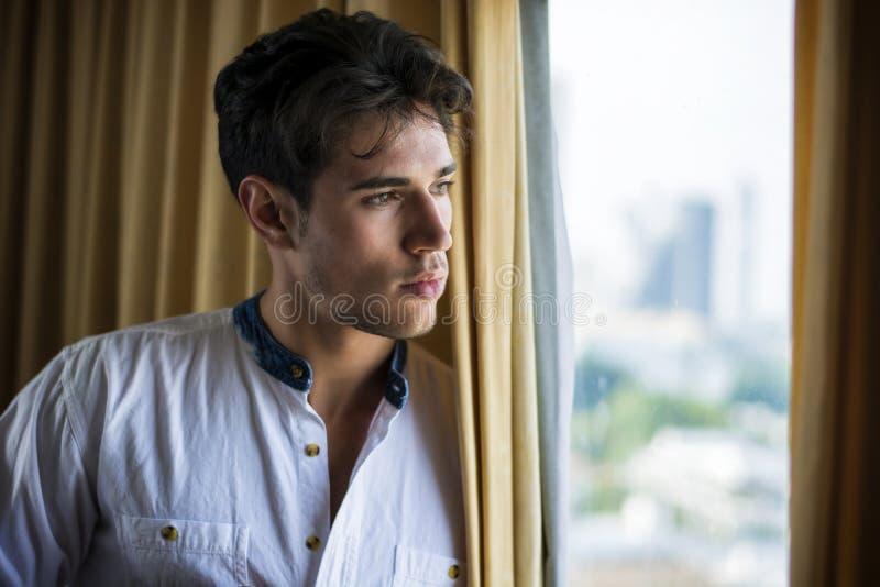 Habillage sexy de jeune homme par des rideaux en fenêtre photo stock