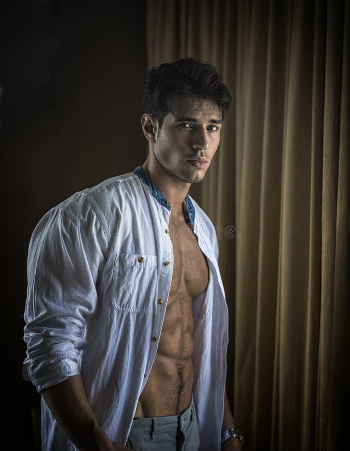 Habillage sexy de jeune homme par des rideaux en fen?tre image stock