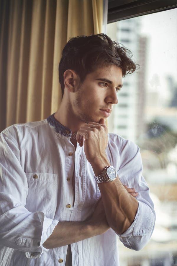 Habillage sexy de jeune homme par des rideaux en fen?tre photos stock