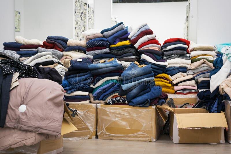 Habillement courant - jeans de collection d'A, chandails, vestes dans l'entrepôt de distribution moderne dans le mail Inventaire, photo libre de droits