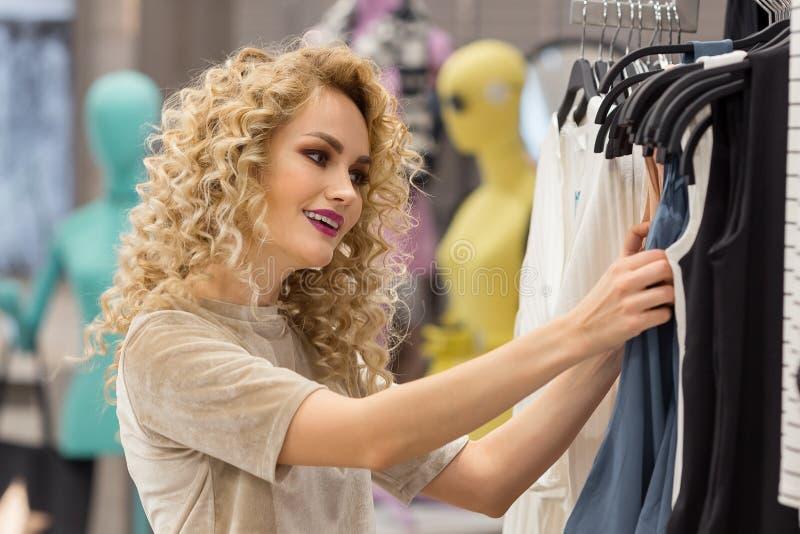 habillement, mode, style et concept de personnes femme heureuse choisissant des vêtements photo stock