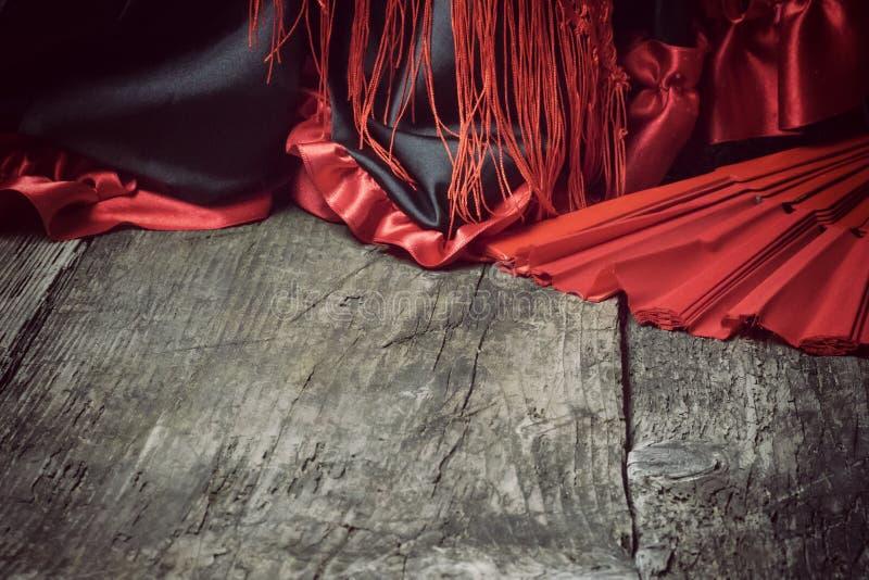 Habillement pour la danse de flamenco et la fan rouge sur le bureau en bois photo stock