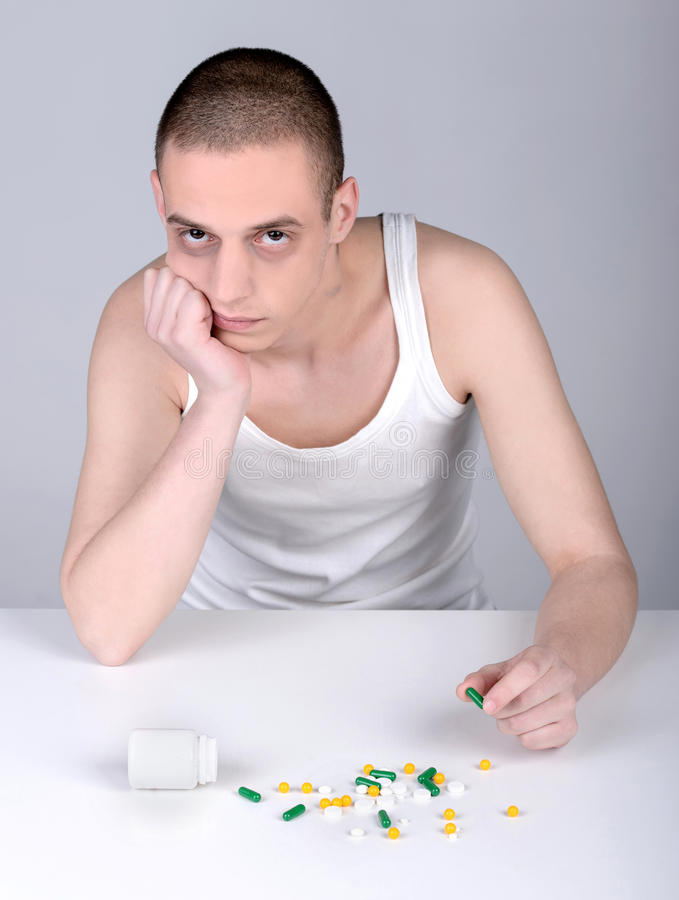 Habit. Portrait of a young drug user on a gray background stock photos