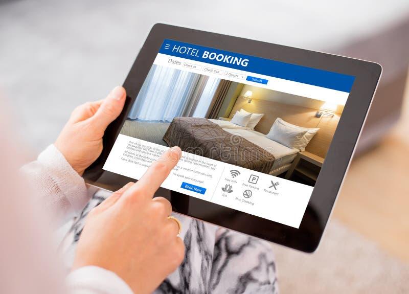 Habitación de la reservación de la persona en la tableta imagenes de archivo