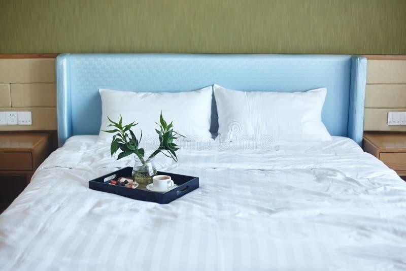 Habitación de lujo con la bandeja del desayuno de la cama con café y frutas Buen servicio del complejo playero Fondo acogedor de  fotografía de archivo