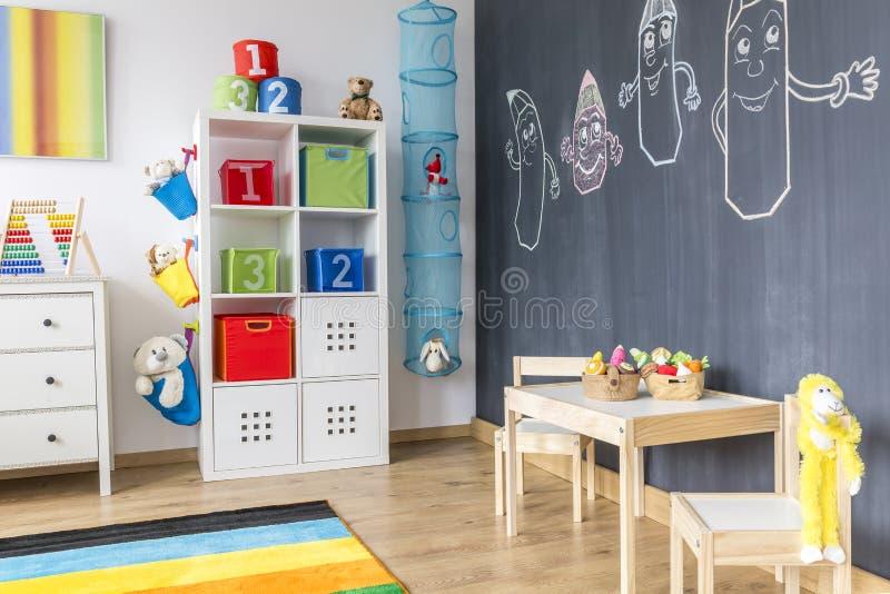 Habitación del niño con la pared de la pizarra imagenes de archivo