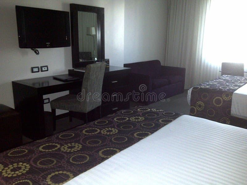 Habitación espaciosa con dos camas matrimoniales, el escritorio cómodo y la TV para el alojamiento de la huésped imagen de archivo libre de regalías