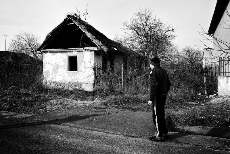 Habitante velho na frente de uma casa velha de Jurilovca foto de stock royalty free