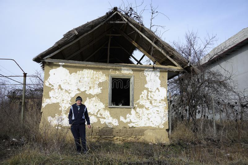 Habitante velho na frente de uma casa velha de Jurilovca imagens de stock