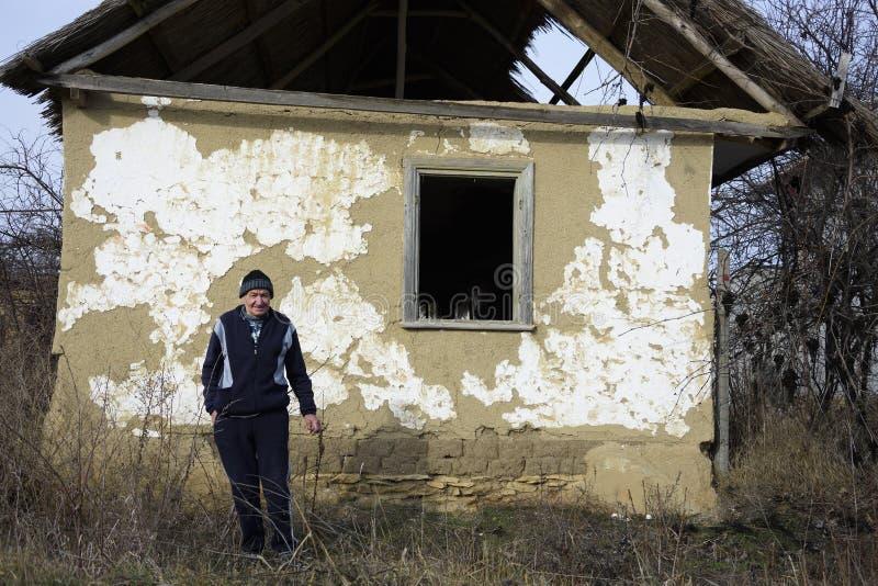 Habitante velho na frente de uma casa velha de Jurilovca foto de stock