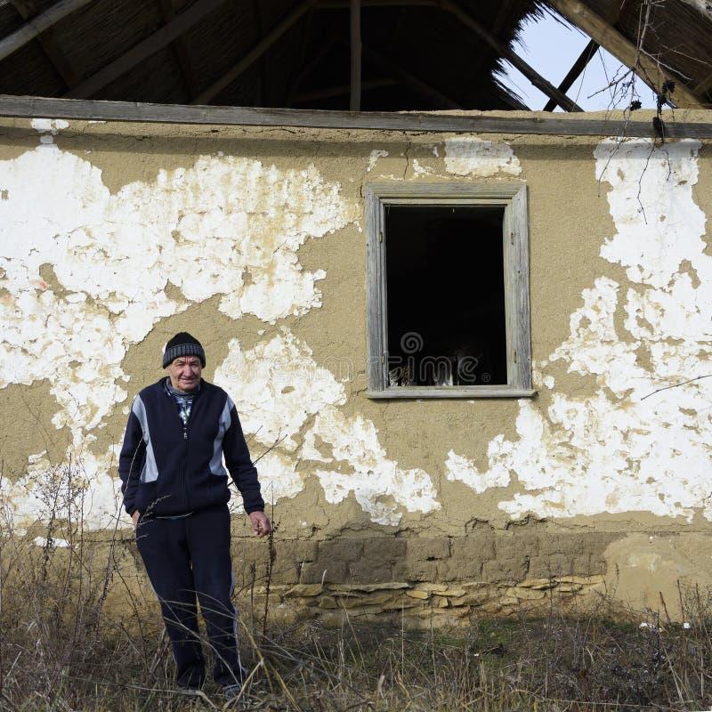 Habitante velho na frente de uma casa velha de Jurilovca imagens de stock royalty free