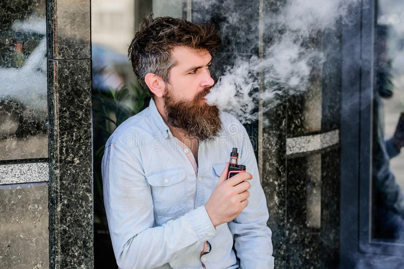 Habits concept. man smoking e-cigarette. hipster man hold vaping device. Mature hipster with beard. Health safety and royalty free stock image