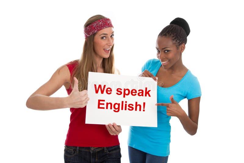 Hablamos inglés - dos mujeres aisladas en blanco imagenes de archivo