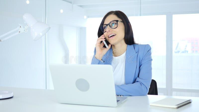 Hablando en el teléfono, empresaria joven que asiste a llamada en el trabajo fotos de archivo