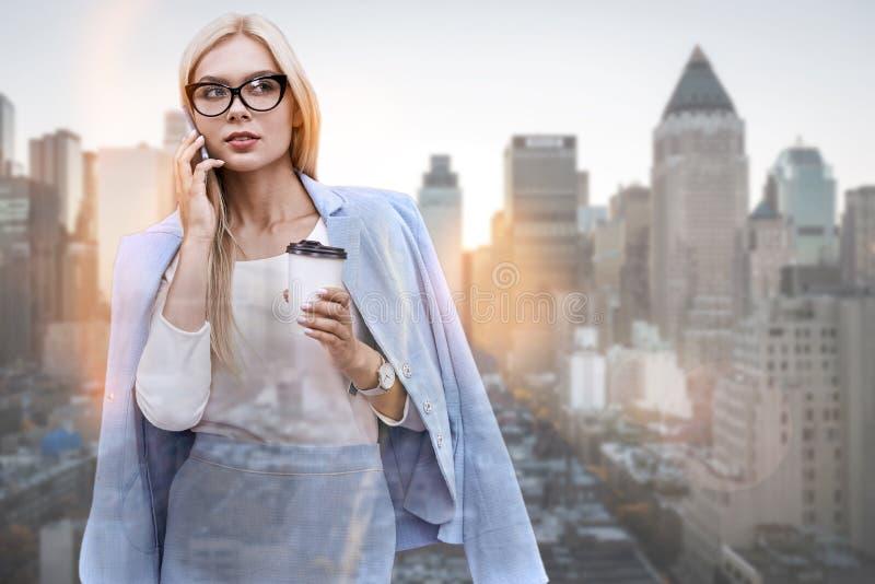 Hablar del contrato Mujer joven hermosa en desgaste clásico que habla en el teléfono y que lleva a cabo la taza de rato del café fotografía de archivo