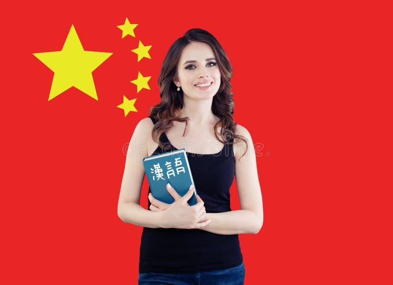 Hable el concepto chino Mujer feliz contra el fondo de la bandera de República Popular China fotografía de archivo libre de regalías