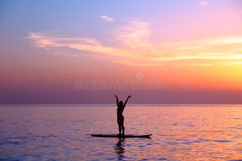 Hacer asanas de la yoga en la playa imagenes de archivo