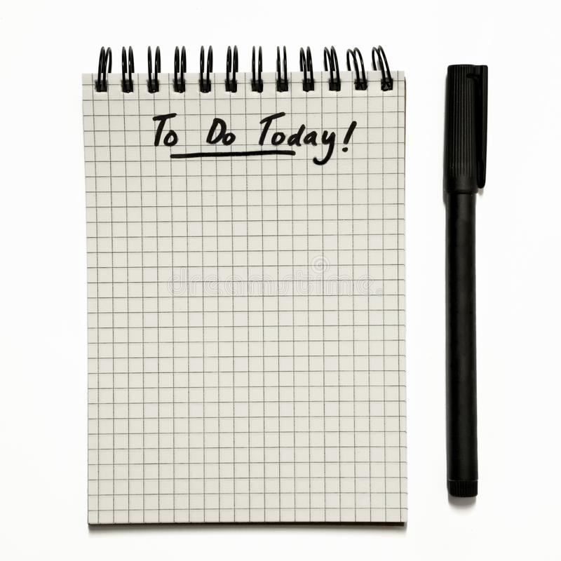 - Hacer la lista en la libreta espiral cuadriculada con la pluma, urgente - aislado hoy en blanco imágenes de archivo libres de regalías