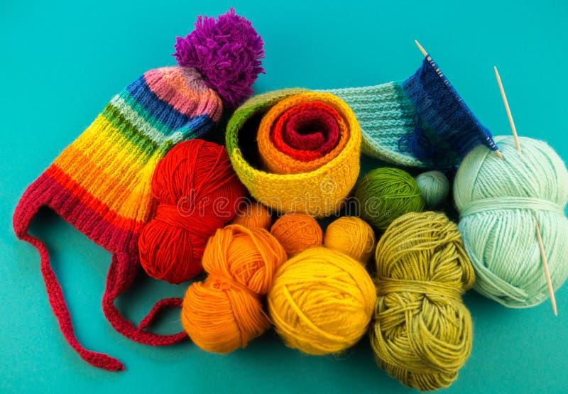 Hacer punto un fondo del azul de la bufanda y del sombrero del arco iris fotografía de archivo