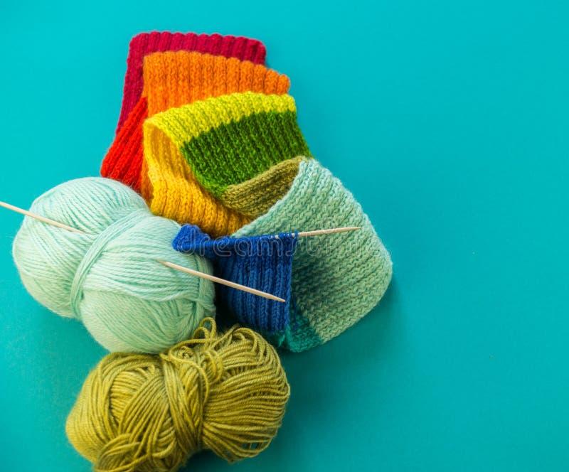 Hacer punto un fondo del azul de la bufanda y del sombrero del arco iris imágenes de archivo libres de regalías