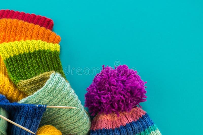 Hacer punto un fondo del azul de la bufanda y del sombrero del arco iris imagen de archivo libre de regalías