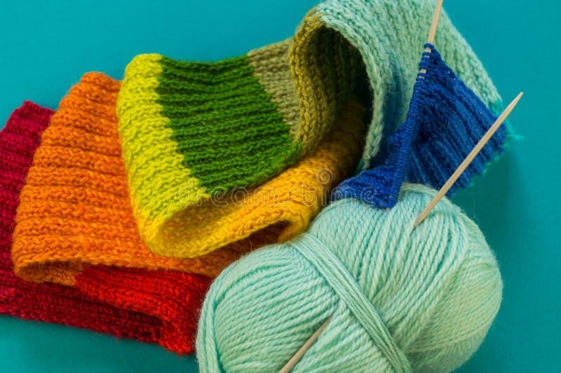 Hacer punto un fondo del azul de la bufanda y del sombrero del arco iris foto de archivo libre de regalías