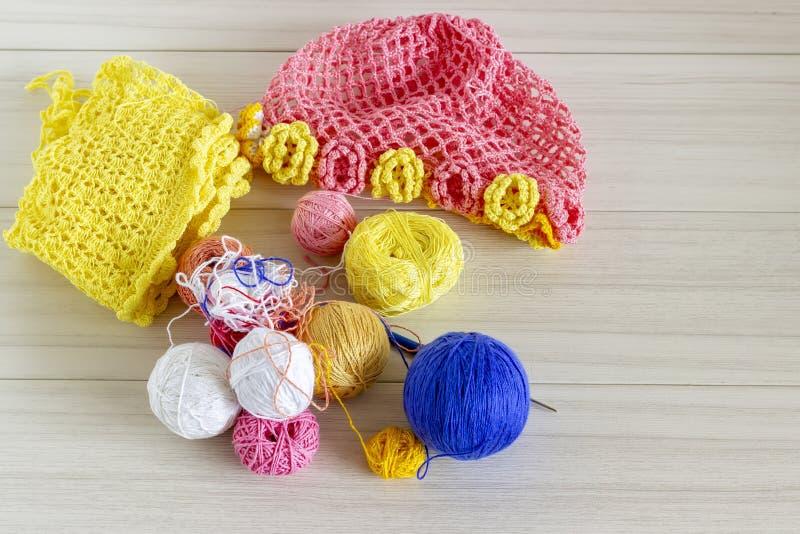 Hacer punto un sombrero de los niños Los hilos coloreados y los sombreros de los niños hechos punto mienten en la tabla Fondo bla fotografía de archivo libre de regalías