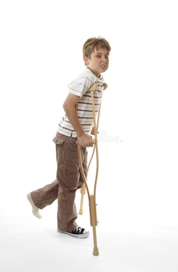 Hacer una mueca de dolor al muchacho dañado que usa las muletas foto de archivo