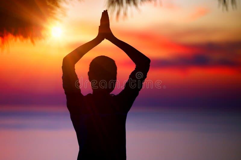 Hacer yoga en puesta del sol foto de archivo libre de regalías