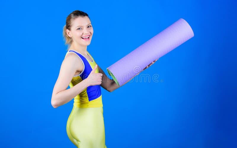 Hacer yoga Equipo de la estera del deporte Aptitud atlética Entrenamiento deportivo de la mujer en gimnasio Músculos fuertes y po fotografía de archivo libre de regalías